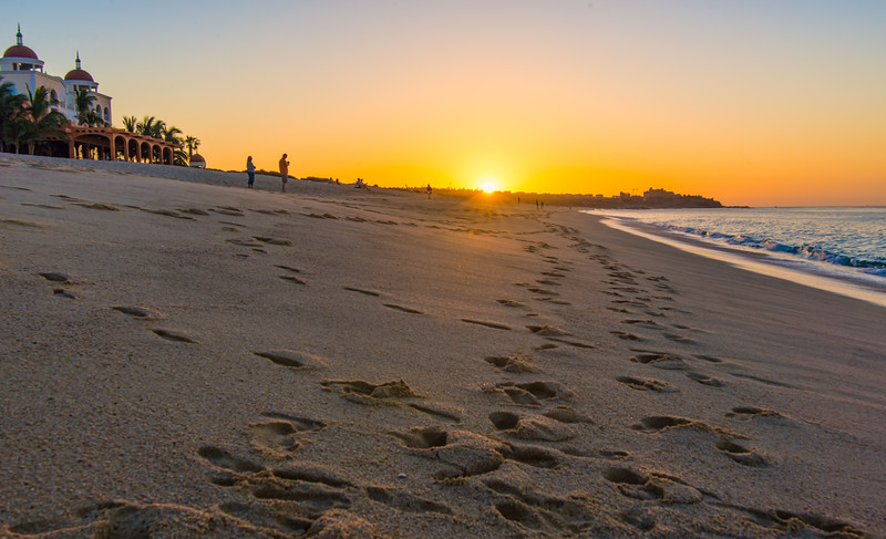 Footsteps in sand on beach at sunrise