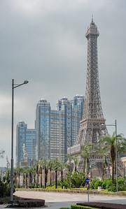 The miniature Eiffel tower in front of The Parisian Macau and behind hotel: Studio City Macau