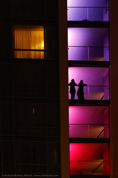 A couple stand on a balcony of a high rise building, silhoetted against colored lights.