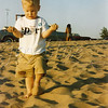 <b>Ain't life grand? NOS in Michigan—July 1995</b>  I wish I had asked my baby boy what he was thinking as he was walking on the beach (and written it down).I've always loved this image (the imperfections of this scan-from-print-from-film aside)—his involvement, the sand slipping from his fingers, and the sand he's kicking up.