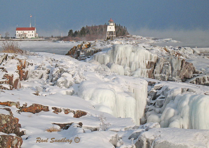 Winter in Grand Marais<br /> <br /> The temperature almost hit rock bottom over the weekend. This morning it was minus 26 degrees with a wind chill of minus 50. It is tough to go out on days like that but it is the high winds and cold temperatures that produce beautiful ice that coats the rocks along the Lake Superior shoreline. I was out on the rocks in the Grand Marais harbor yesterday afternoon to get the attached photo. I was the only one out taking in the exceptional beauty of the lake. I could understand why I was alone when my hands almost froze to the camera.
