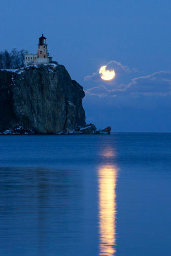 Split Rock Moonrise 003 Jan 22<br /> <br /> It wasn't long before the orange globe slowly ascended in front of the cliff. A few clouds covered the horizon adding to the ambiance of the evening. As the moon broke through the clouds appeared like arms and caressed the moon.