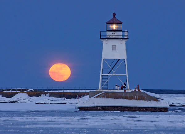 Grand Marais Moonrise 001<br /> <br /> The forecast was for partly cloudy skies as we drove to Grand Marais to photograph the full moon. March is the month the moon rises behind Artist's Point and the lighthouse. The bay was ice covered even though huge waves were coming in. I hoped that there would be a break in the clouds so we could see the moon. It wasn't long before that orange ball slowly started coming up over the lake and the clouds opened.<br /> <br /> A family was taking in this beautiful scene from the base of the lighthouse. I wondered if they planned on being at the end of the breakwall when the full moon appeared or if this was just icing on the cake of a great North Shore vacation.
