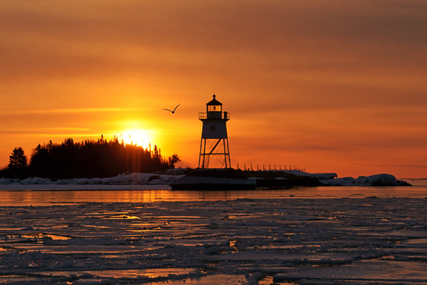 Grand Marais Sunrise 001<br /> <br /> I returned at sunrise. During the night, the ice broke up in most of the bay and huge pieces were being carried out onto the lake. The sunrise was as beautiful as the evening's moon. A few gulls had returned and one circled the lighthouse just as I took its picture.<br /> <br /> Paul & Karla