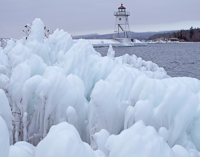 Grand Marais Harbor 004<br /> <br /> Both Grand Marais break walls are covered with ice. It is amazing how ice can form into so many beautiful shapes and designs. With the present forecast it looks like the ice will last for some time so many people will have an opportunity to enjoy the wonderful sculptures over the holidays.