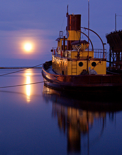 Moonrise Over the Edna G<br /> <br /> There are many places along Lake Superior to watch the moonrise but in July Agate Bay is hard to beat. In this photo it appears that the moon is lighting up the edge of the Edna G. Actually it is the revolving light of the Two Harbors lighthouse that is reflecting off the yellow paint. This is a 25 second exposure so that the beam of light from the lighthouse is hitting the Edna G several times while exposing the picture.