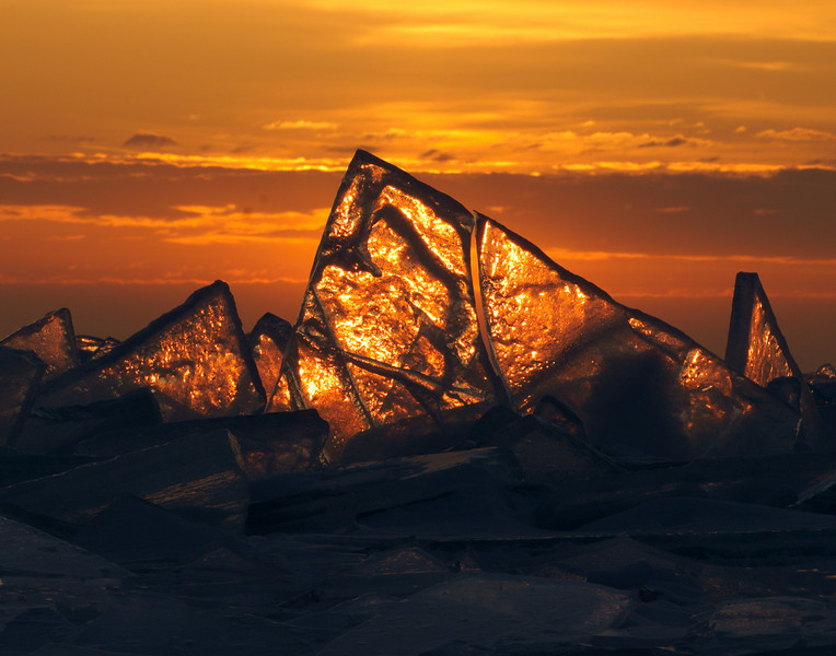 Sunrise on the Ice Shards<br /> <br /> The ice takes on a whole different view at sunrise. If you look at the center of the largest shard it looks like a fisherman in his boat getting ready to cast his nets.