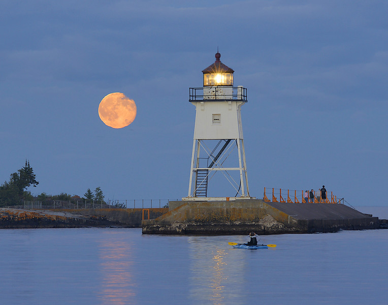 Grand Marais Light<br /> <br /> The next night I was in Grand Marais as the moon rose next to the Grand Marais Light. Many people were out enjoying the moonrise. Even some kayakers had to stop and photograph the moon.