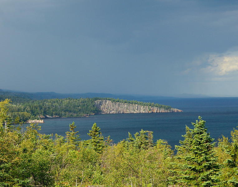 Rain Storm Over Shovel Point 001<br /> <br /> In the process of moving this week I went into Silver Bay to rent a trailer. While getting back on Hwy 61 I noticed a small storm that looked like it was going to pass over Palisade Head. I have always wanted to get a good rainbow shot of Shovel Point from Palisade Head so I made a change in plans and headed up to the top of the overlook. I was not disappointed. The raincloud was just passing over Shovel Point when I got to the top.