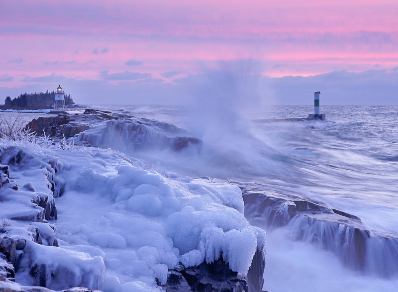 Grand Marais Harbor 001<br /> <br /> Earlier in the week large rollers hit the North Shore. Combined with the colder temperatures, spray from those rollers froze on the rocks creating beautiful ice sculptures. The waves that crashed onto the shore were very powerful and noisy, but when photographed at a slow shutter speed seemed to be transformed into a tranquil panorama. This photo was taken at sunrise just outside of the Grand Marais Harbor. The sun cast a pink hue on the horizon for just a few minutes. I was glad I was there in time to see it.