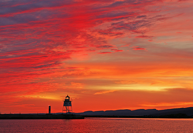 Sun Pillar Over Grand Marais Light 001<br /> <br /> This weekend a snowstorm moved into northern Minnesota and dropped several inches of snow. Prior to a storm can be a good time to get some great sunset photos. I went to town on Friday night and I couldn't have gone at a better time. It was one of the prettiest sunsets I have seen all year. <br /> The reds were incredibly vibrant as a small sun pillar formed over the lighthouse. Sun pillars form when the ice crystals in the upper atmosphere reflect the sunlight back to earth. A friend in Two Harbors also saw the sun pillar so anyone watching the evening sky from Two Harbors to Grand Marais got the opportunity to see a pretty good show.