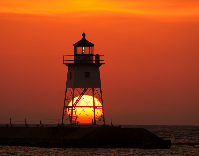 Grand Marais Harbor Sunrise 001<br /> <br /> Earlier in the week there was enough cloud cover that I was able to capture the sun rising and setting below the lighthouse.