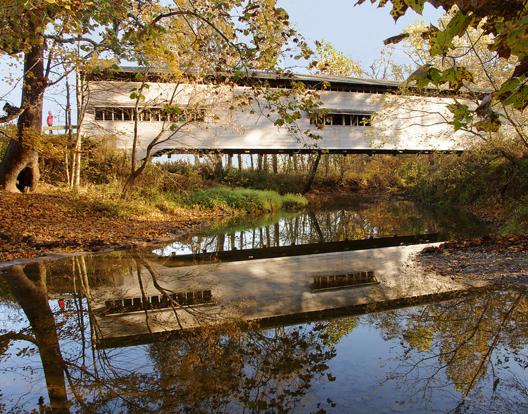"Covered Bridge<br /> <br /> Coming across Indiana we saw a few of the covered bridges that are still in use in Parke County. There are 39 covered bridges in the county but we only had time to see three.  We almost missed this beautiful bridge but Karla spotted it on the map and directed us to the spot. We had to take some pretty narrow back roads to get there.  We noticed a sign that said ""Trespassers Will Be Shot"".  I wanted to go back and take a picture, but Karla didn't think that was a good idea."