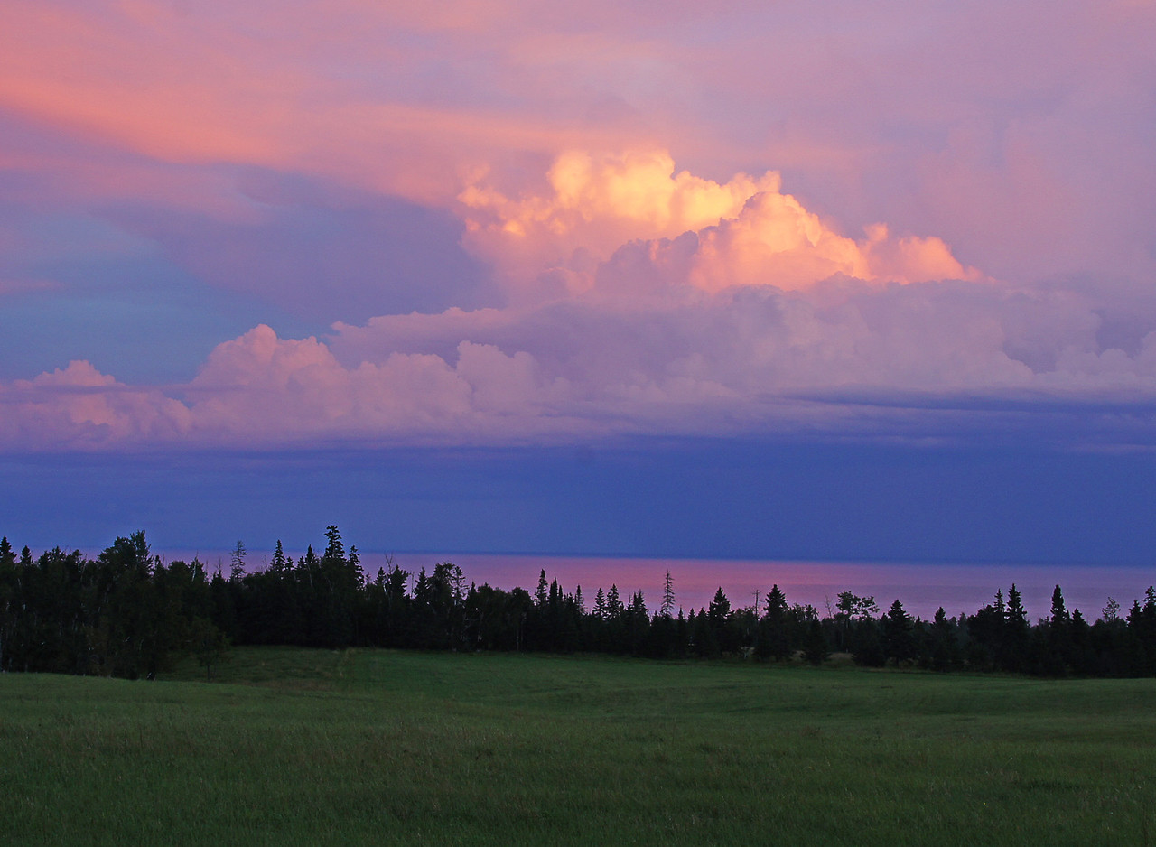 Storm Over Grand Marais 009<br /> <br /> On my way home I stopped in the field below our house and watched the clouds turn orange from the setting sun. Every so often a lightning bolt would come straight down hitting Lake Superior.