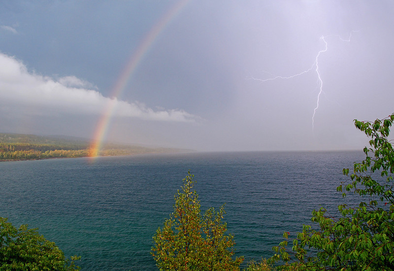 Storm Over Lake Superior<br /> <br /> We had another series of storms pass over Lake Superior. It appeared like the sun might show behind the clouds so I drove down to the Cutface Wayside to see if I couldn't get a photo of a rainbow should one appear. As soon as the storm moved out over the lake the sun's rays started to light up the trees over the Sawtooth Mountains. Then all of a sudden out came the rainbow.  With the dark clouds behind, the colors were even more intense.<br />  <br /> I set up the tripod alongside HWY 61 and started to take some photos. The storm wasn't done yet as lightning was striking the water about every 30 seconds.  I was shooting the rainbow photos at 1/40 of a second so I never thought that I would be able to capture any of the lightning strikes since they are way faster than that. I took about twenty images and was very surprised to find that one of the photos did capture a bolt of lightning right before it entered the waters of Lake Superior.