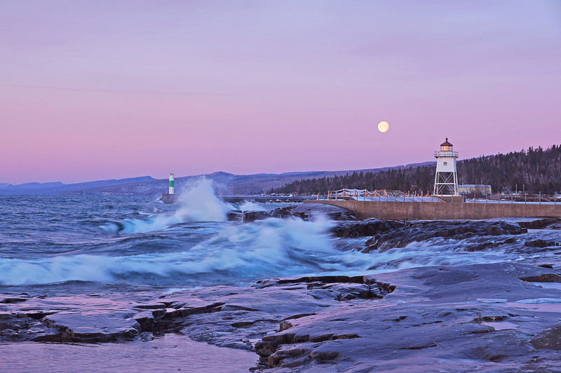 Moonset Over Grand Marais<br /> <br /> The next morning I drove into Grand Marais to watch the moon set behind the lighthouse. Lake Superior was more active with lots of waves crashing into the shoreline.