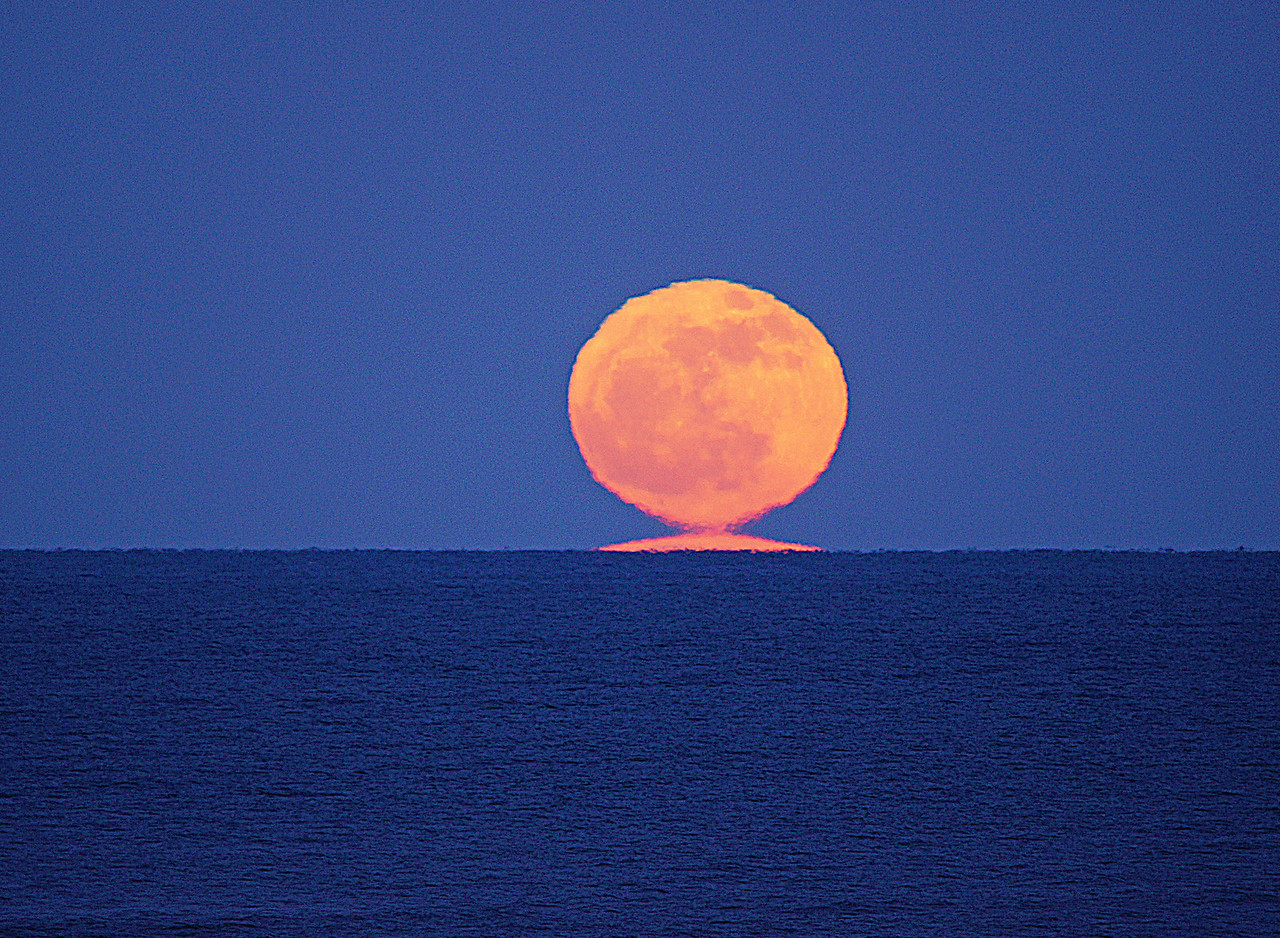 """Melting Snow Moon 002<br /> <br /> According to Spaceweather.com, folklore describes this natural special effect as the """"Snow Moon."""" The melting moon is a mirage, caused by sun-warmed air over Lake Superior's surface. The temperature profile turned Earth's atmosphere into a lens, refracting the rays of the rising moon and distorting the lunar disk. You can see an inverted moon beneath the """"real"""" one."""