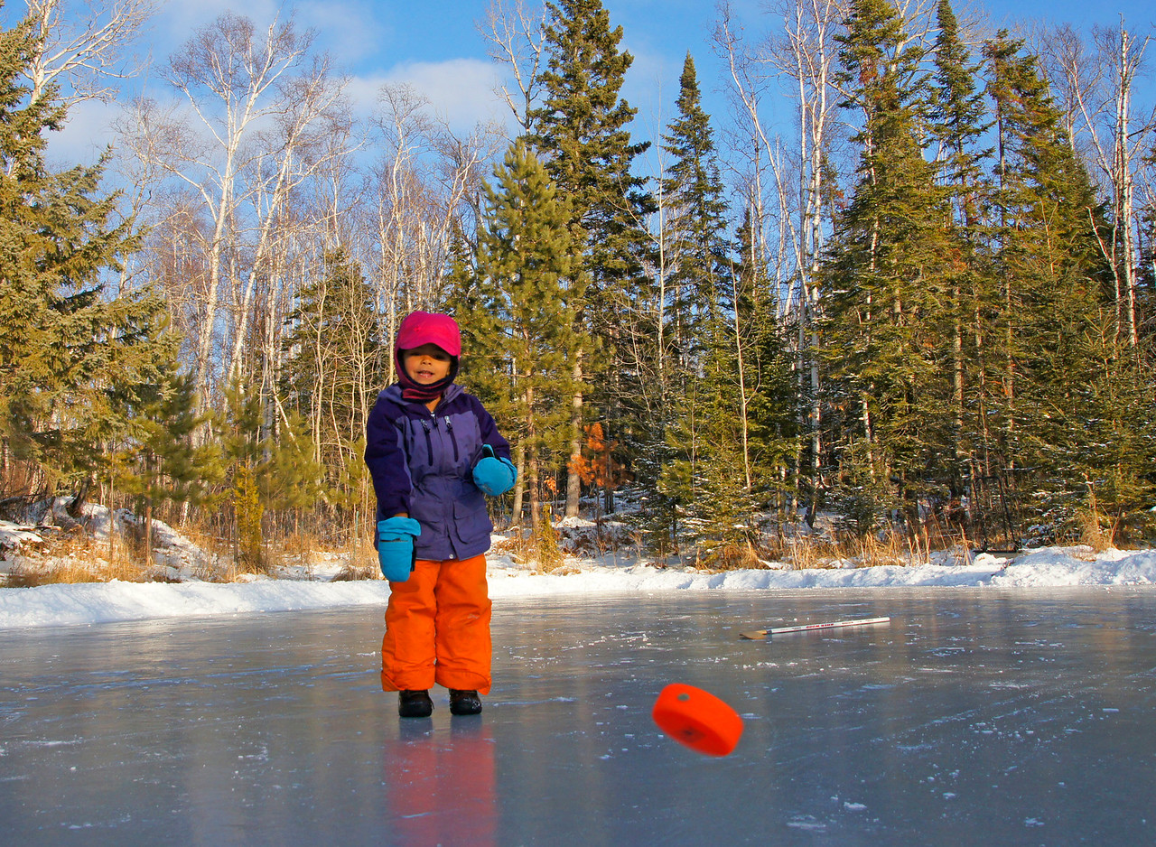 Playing Hickey Pocks<br /> <br /> She has not learned to skate but enjoys sliding on the ice and knocking around the hockey puck which she calls hickey pocks.