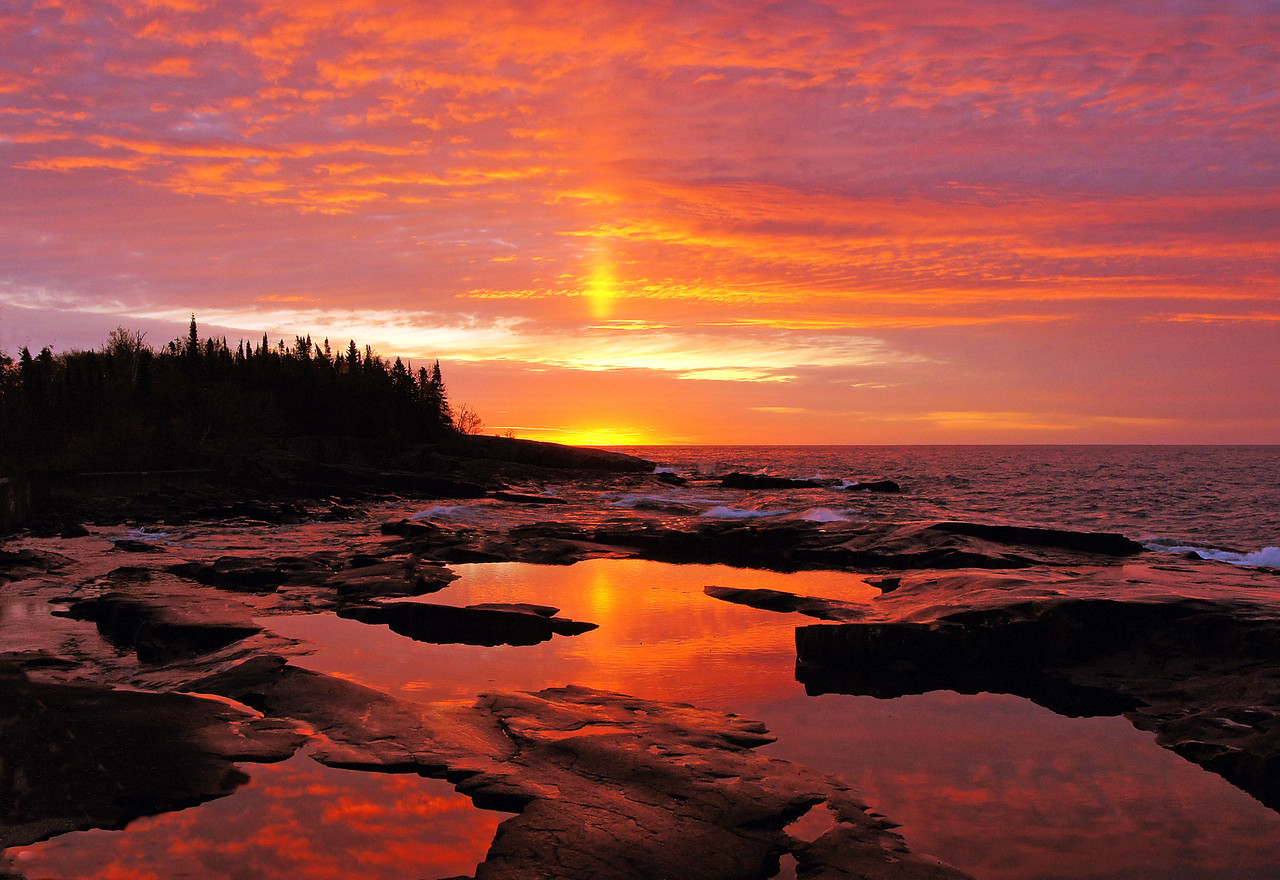 Grand Marais Sunrise 001<br /> <br /> With the unsettled rainy weather this week we had both a great sunrise and sunset over Lake Superior. The sunrise which included a beautiful sun pillar occurred on Monday, October 8.  I went to Artist Point in Grand Marais to photograph the sunrise reflected in the small pools of water in front of the break wall. I get to see a sun pillar about twice a year and this one was pretty spectacular. A sun pillar forms when cold, calm air creates ice crystals in the upper atmosphere.  The sunrise then reflects off the ice crystals.