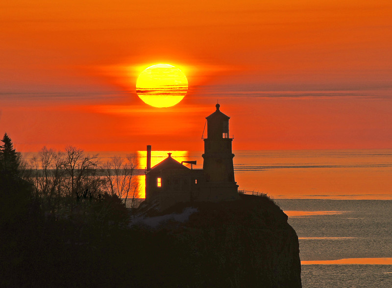 Sunrise Over Splitrock Lighthouse<br /> <br /> This time of year you can photograph the sun rising behind Split Rock Lighthouse. This photo was taken from the Hwy61 rest area overlooking Split Rock Lighthouse State Park just a couple of days ago. There was just enough cloud cover to bring out the beautiful colors in the sun while skim ice covering part of Lake Superior created the beautiful reflections.