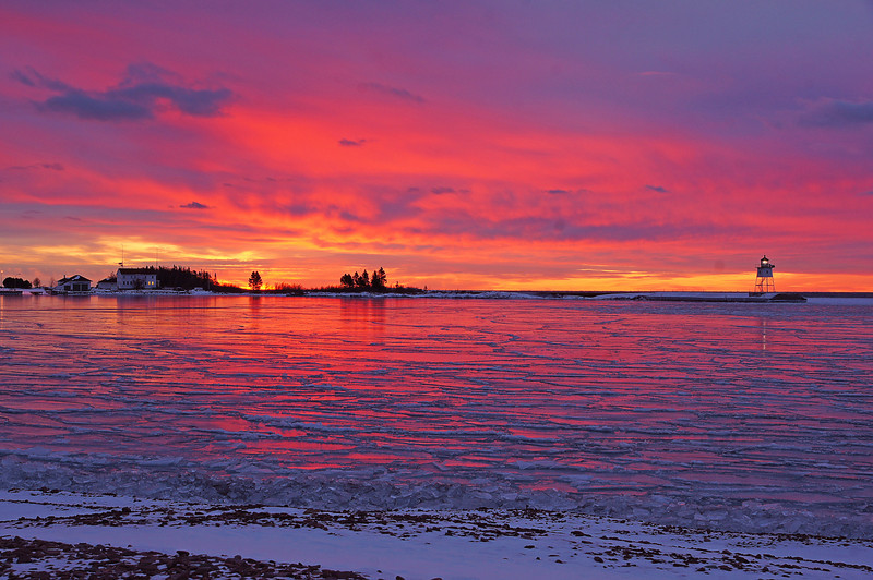 Grand Marais Harbor<br /> <br /> Yesterday we had a beautiful sunrise over the Grand Marais Harbor. Usually right before big storms we get beautiful sunrises. Now the storm is in progress and the snow is piling up.