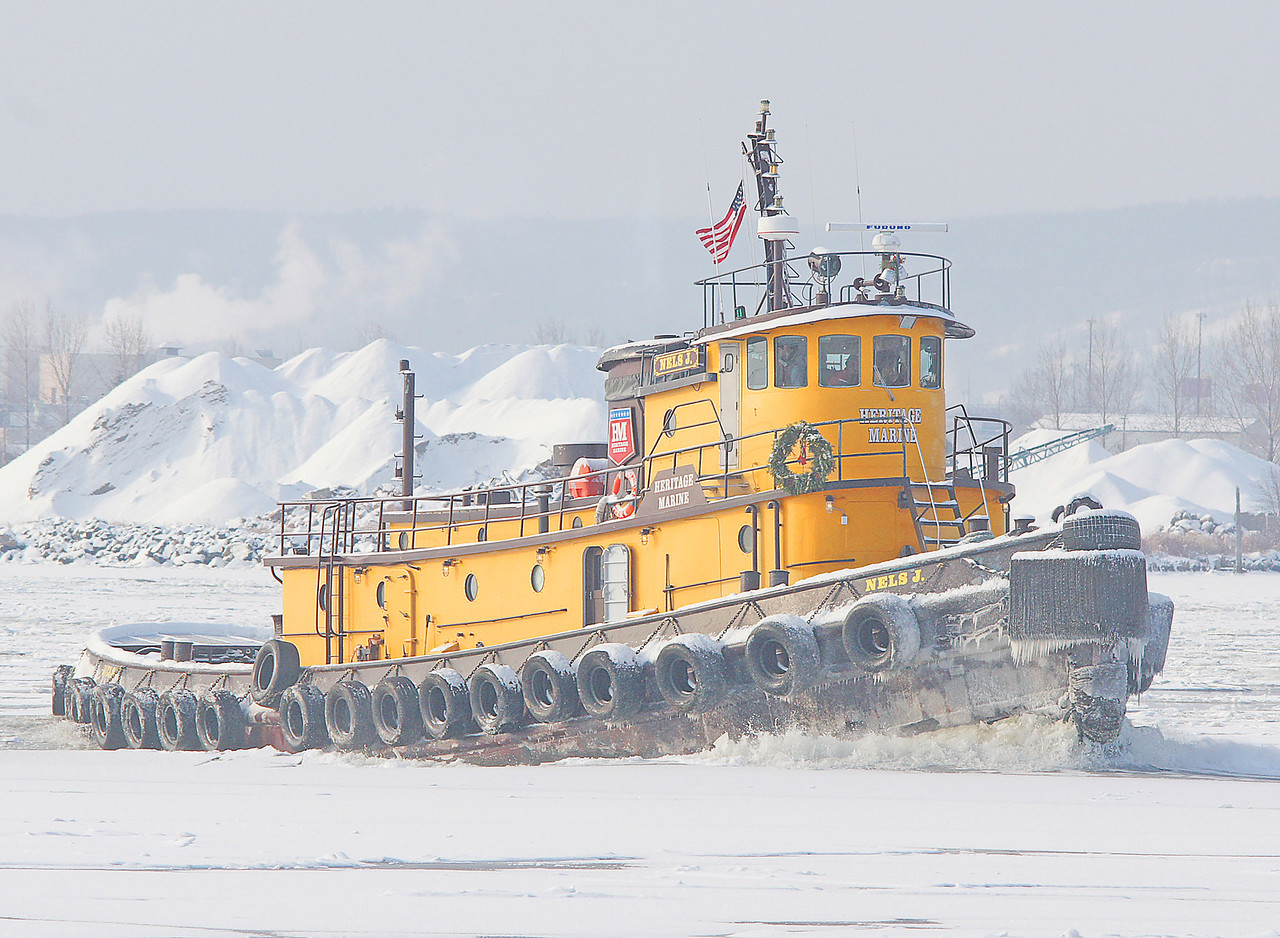 Nels J Tugboat<br /> <br /> Two Duluth based tugs assisted. The Nels J. shown here is 103 ft long and has a 16 cylinder diesel engine capable of 1,950 horsepower. The sounds of the huge ice chunks hitting the bottom of the tugs were pretty impressive.