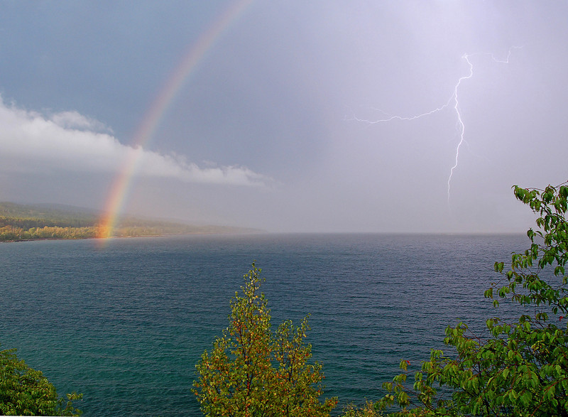 Lightning Over Lake Superior<br /> <br /> A passing storm produced a beautiful rainbow as the sun peeked out from behind the clouds. Just as I took this photo a lightning strike hit the surface of Lake Superior.