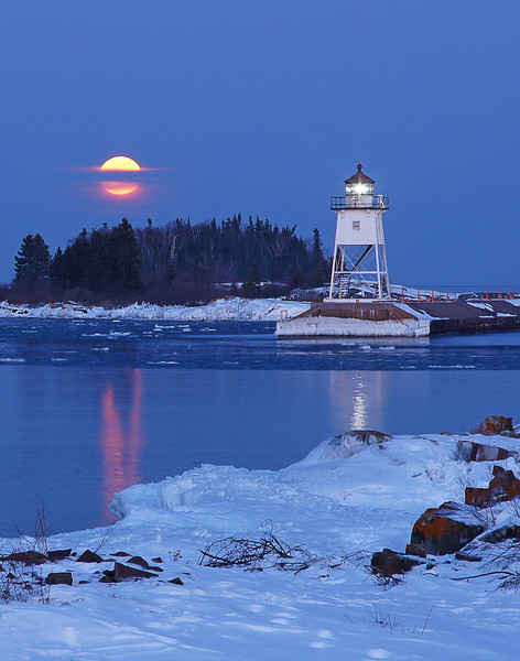 Feb Full Moon Over Grand Marais Harbor 002<br /> <br /> We thought the clouds along the horizon were going to block the moon's appearance; however, they actually enhanced the photo opportunity by creating a band that the moon had to pass through.