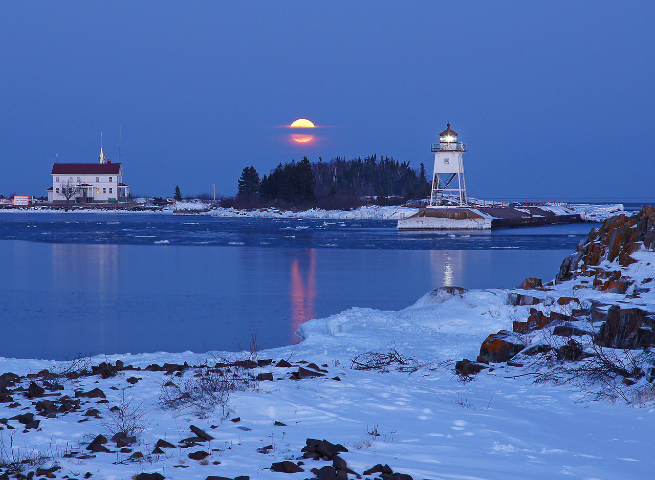 Feb Full Moon Over Grand Marais Harbor 001<br /> <br /> We had an awesome evening as we watched the full moon rise above the Grand Marais harbor. Floating ice reflected not only the full moon but also the light from the lighthouse adding to the magic of the evening.