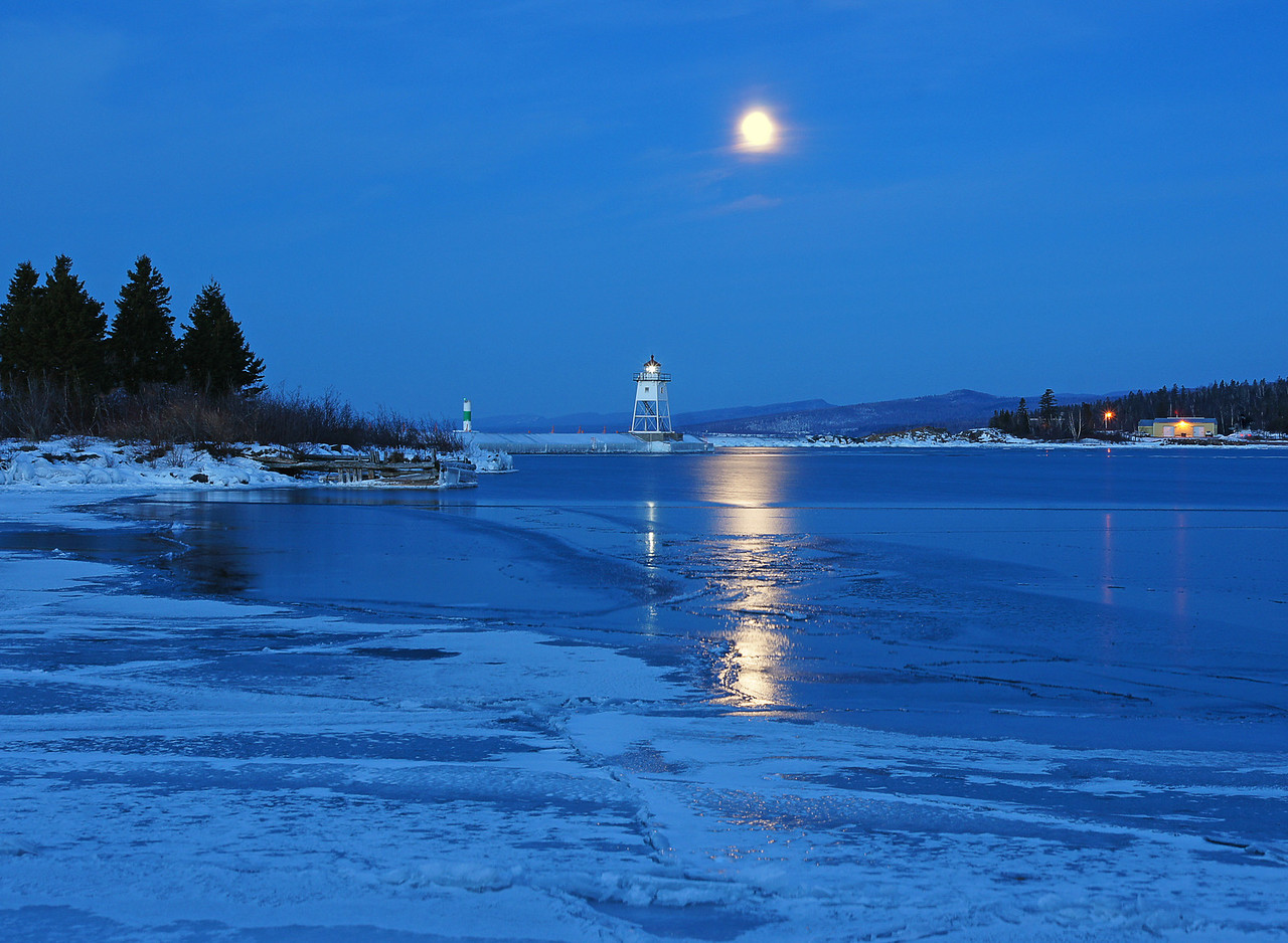 Feb Full Moon Setting on Grand Marais Harbor 001<br /> <br />  Early the next morning I went back into Grand Marais to photograph the setting of the moon. These photos were taken across the harbor from where the evening photos were shot. Again the reflected light on the ice sheets added to the experience.