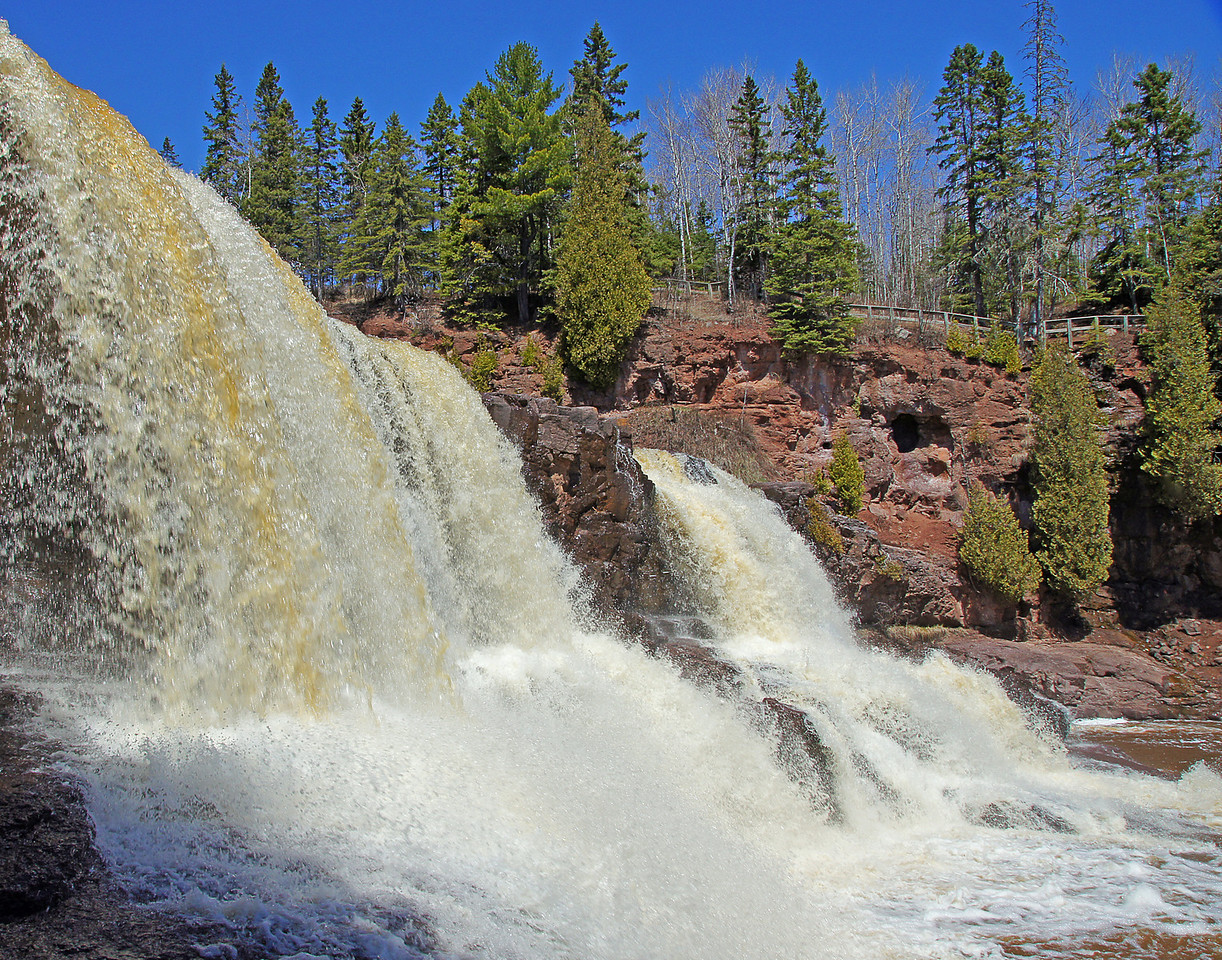 Middle Gooseberry Falls 001<br /> <br /> I think spring has finally arrived on the North Shore.  There is plenty of water cascading over the waterfalls which makes hiking along the rivers very enjoyable.  We hiked two of the rivers this week. I took this photo of the Middle Falls on the Gooseberry River with a clear blue sky in the background.