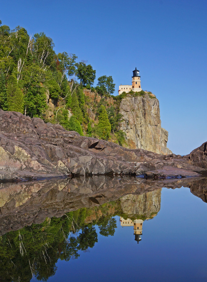 """Split Rock Reflections 002<br /> <br /> One of the last times that I tried this I was lying by the pool looking through the viewfinder of the camera. Since there was a light breeze it took several minutes for the pool of water to calm down. I glanced up at the lighthouse and noticed a crowd was forming and they were all looking down in my direction. It occurred to me that since I had been lying so still for several minutes they probably thought I was hurt. All of a sudden a young boy came quickly down the trail and saw me move and said, """"Oh, you're ok, everyone up there thinks you have had a heart attack. My mom sent me down here to check it out."""" Now I move around a little more when I am taking those photos."""