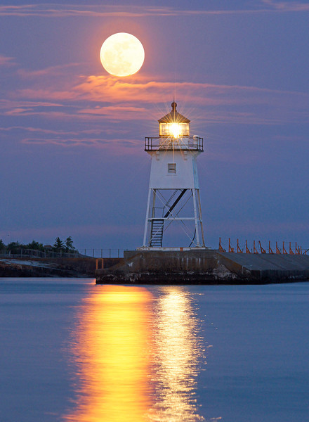 August Full Moon Grand Marais Harbor<br /> <br /> There were three consecutive nights in August that the full moon rose early enough to get a good photograph.  The first night was too cloudy, the second night was foggy and only the third night worked out. There were clouds also that night but I went to the Grand Marais harbor just in case the clouds broke up. My GPS indicated that the moonrise was around 8:33 PM. I waited and waited but saw no moon. I decided the clouds were too thick so I took the camera off the tripod, placed it in the car and headed for home.<br />  <br /> As I was leaving town I decided to take one more look. I looked back and just a sliver of the moon was starting to break through the clouds so I turned around and headed back to the beach. I quickly grabbed by camera and reached for my tripod but it wasn't in the back seat. I looked over to where I was parked before and saw my tripod sitting in the middle of the parking lot where I had left it earlier. Luckily it was still there. <br /> <br /> The evening ended well as I got the photo I was after and I also got my tripod back.<br /> <br /> Note: to get this photo I had to use one photo with the lighthouse properly exposed and another one with the moon not burned out. I then combined them.