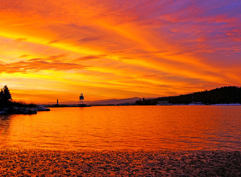 "December 18 Sunset Grand Marias<br /> <br /> This afternoon Karla and I discussed not having any photos for ""Photo of the Week"".  My last chance was to drive into Grand Marais for a sunset. Watching the clouds moving in from the west it looked promising but I never imagined just how good it was going to be.<br />  <br /> After the sun disappeared below the horizon the clouds turned many shades of red, orange and yellow. I stood there in awe at the wonder of creation. Dozens of people, with cameras in hand, were able to experience this sunset.  <br /> <br /> When a sunset is this beautiful, I take several photos from many different angles to find the right composition. This one was my favorite.<br /> <br />  We want to wish everyone a very Merry Christmas."