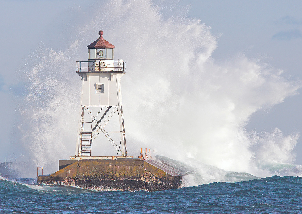 High Waves Grand Marais Lighthouse 001<br /> <br /> We had some pretty strong onshore winds earlier this week. I didn't realize that the waves were coming in with such force until I drove into Grand Marais. I went down to the harbor to get some shots from the point but the spray was coming over the rocks making it impossible to use a camera.