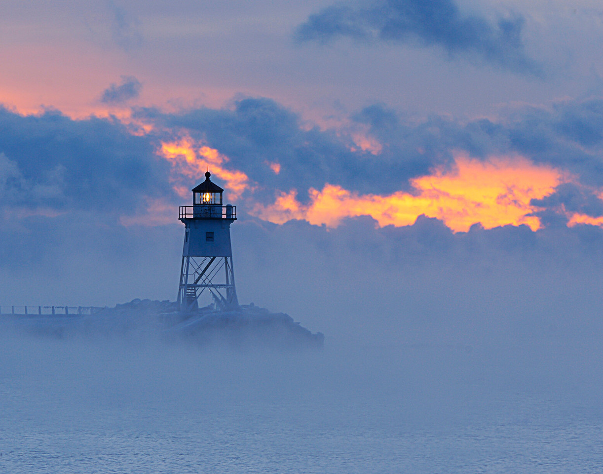 Grand Marais Light 001<br /> <br /> The thermometer read minus 12 degrees with the wind chill around minus 30. I wasn't sure I wanted to go outside but I knew that the cold off shore winds would create sea smoke outside of the Grand Marais Harbor.  Some of the most beautiful colors imaginable can be seen when the rising sun shines through sea smoke.  At the harbor the sky appeared as though someone had set the clouds on fire.
