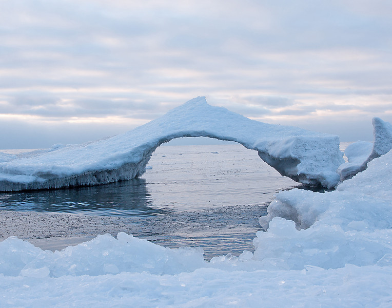 Ice Bridge 001<br /> <br /> This week Travis Novitsky, a friend and local photographer from Grand Portage, e-mailed to tell me that the onshore winds were piling the ice up east of Grand Marais. The waves were eroding the piles of ice and turning them into beautiful arches.