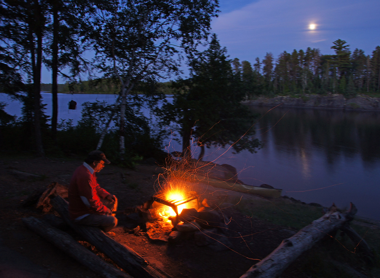 Evening Solitude<br /> <br /> We planned our trip to coincide with the full moon but clouds got in the way and let the moon show through for only a short period of time. We sat around the campfire for hours listening to the loons. At one time there were four loons calling from all sides of the lake. The call of the loon is delightful wilderness music to lull a person to sleep. <br /> <br /> If you are wondering why our food pack is hanging in the tree in this photo that is how to keep it from the bears.