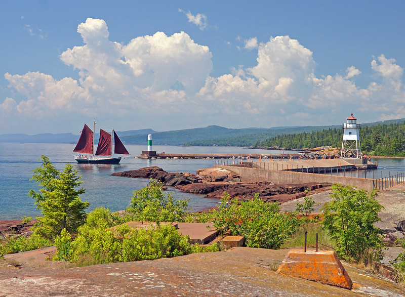 Grand Marais Harbor<br /> <br /> The shores of Lake Superior are inviting but even more so with the intense heat wave that has gripped most of the country. We live only 3 miles from Lake Superior but our thermometer registered 90 degrees.<br />  <br /> We went for a walk on the Grand Marais break wall to cool off and the temperature there was 70 degrees. What a wonderful relief! We sat there for some time watching boats and kayaks as the fog drifted back and forth. At times the fog would completely cover the lighthouse and a few minutes later the lighthouse would reappear.