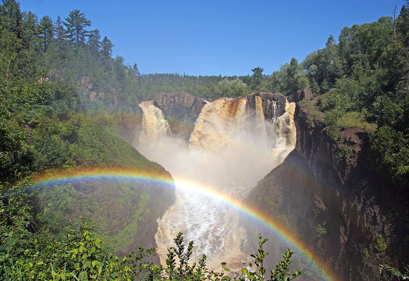 High Falls Grand Portage State Park<br /> <br /> The same rain increased the water levels in most of the north shore streams. At Grand Portage State Park, the amount of water coming over the high falls on the Pigeon River nearly doubled.  With that much water dropping about 125 feet the mist makes for a beautiful rainbow or mist bow. To visualize how large this falls is look at the two people in the upper left hand corner of the photo.