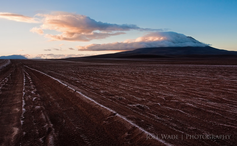 Chasing Sunrise<br /> <br /> In the high desert of Bolivia- known as the Altiplano- at dawn.  I'm in a 4x4 trying to beat the sunrise before it hits a famous rock formation, and losing.  Frost is still sitting on the tire ruts, and the sun starts lighting up clouds formed on an ancient volcano.  If this is losing, I'm OK with that.<br /> <br /> ISO 320, 22mm, f/8, 1/125 second exposure.