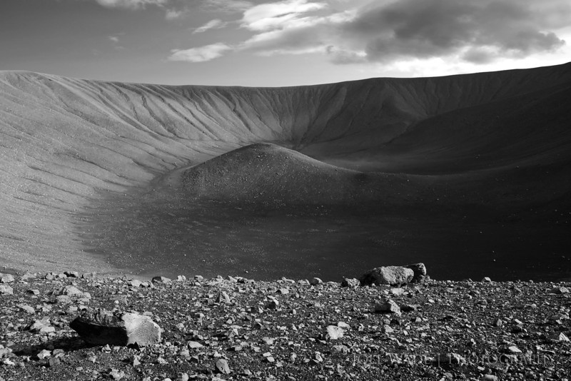 "The Crater – Iceland<br />  <br /> With Iceland and its now-infamous volcanoes in the news so much these days, a shot from a more peaceful volcano seemed in order.  The crater shown here is Hverfjall in northern Iceland, which last erupted a distant 2500 years ago.  The cinder cone shaped crater looks exactly what you'd imagine a volcano should look like with steep, symmetrical sides, but a short hike lets you summit to the top and circle the whole ring of the crater if you don't mind a little slogging.  Iceland sits atop the Mid-Atlantic ridge, and its gorgeous countryside is riddled with volcanic activity old and new, from boiling mud pots, spouting geysers, and pitch-black lava fields to natural hot springs and the occasional not-so-nice-smelling sulfurous hot shower.  There's even local bread that's cooked by burying it in a bucket a few feet underground and letting the geothermal heat cook it.  Tasty!<br /> <br /> ISO 400, 17mm, f/11, 1/250s exposure.<br />  <br /> More shots from the surreal and stunning landscape of Iceland:<br /> <br />  <a href=""http://joelwade.smugmug.com/Places/Iceland/9286017_Scf7n#620246814_aBzMa"">http://joelwade.smugmug.com/Places/Iceland/9286017_Scf7n#620246814_aBzMa</a>"