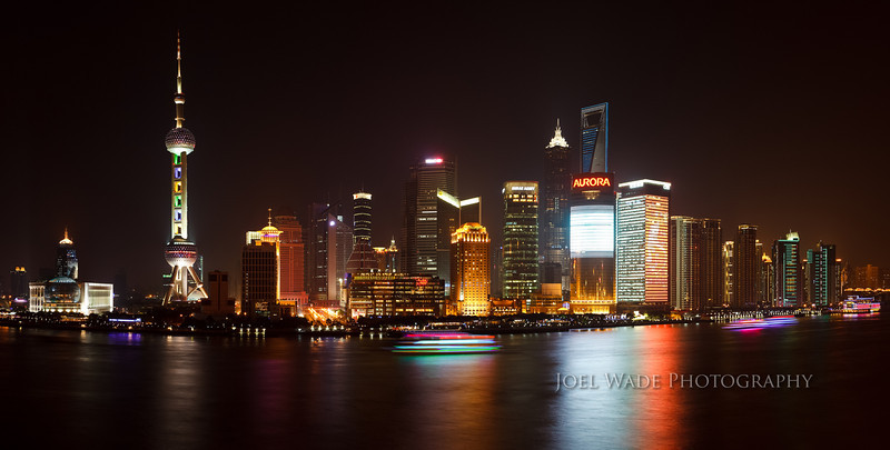 "Happy New Year – New Shanghai<br /> <br /> At the beginning of a new year, a big picture of a new city – the Pudong New Area district of Shanghai, which was completely undeveloped until plans were unveiled for a special economic zone in 1990.  A gentle visual reminder to stay focused on your own ""big picture"", and not let the little trials and tribulations of our lives hold you back or keep you down.<br /> <br /> Tip:  For those who don't tune out at the mention of ""photoshop"", you can put together some stunning panoramas quite easily by stitching together multiple shots into a single composition.  This was assembled from six vertical shots, captured in manual mode on a tripod to keep the exposure consistent from left to right.<br /> <br />  ISO 100, 40mm, f/9, six 8-second exposures."