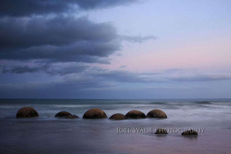 "Moeraki Boulders – New Zealand<br /> <br /> Sometimes the most beautiful light is not during the sunset, but shortly after in what is known popularly as the ""blue hour"".  One of my favorite spots in all of New Zealand was captured here in that light- the Moeraki Boulders- an usual geological formation of near-perfectly spherical boulders.  Setting the camera on a tripod and using a long six-second exposure brought out the detail in the rock textures, while revealing the subtle color changes across the sky.<br /> <br />  ISO 100, 24mm, f/22, 6 second exposure."