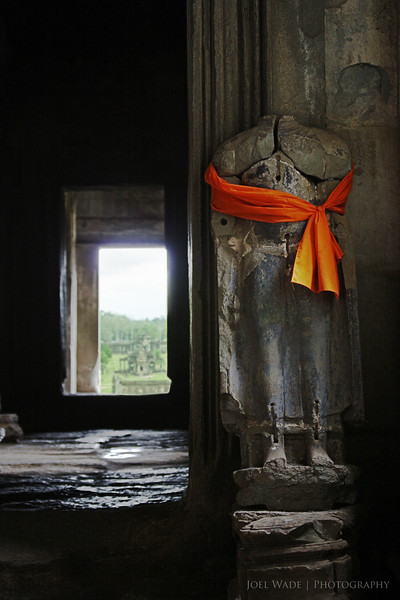 Inside Angkor<br /> <br /> Shot many years ago inside the Angkor Wat temple complex in Seam Reap, Cambodia.  Monks often adorn the many statues with orange sashes.<br /> <br /> ISO 100, 56mm, f4.5, 1/15 second exposure.