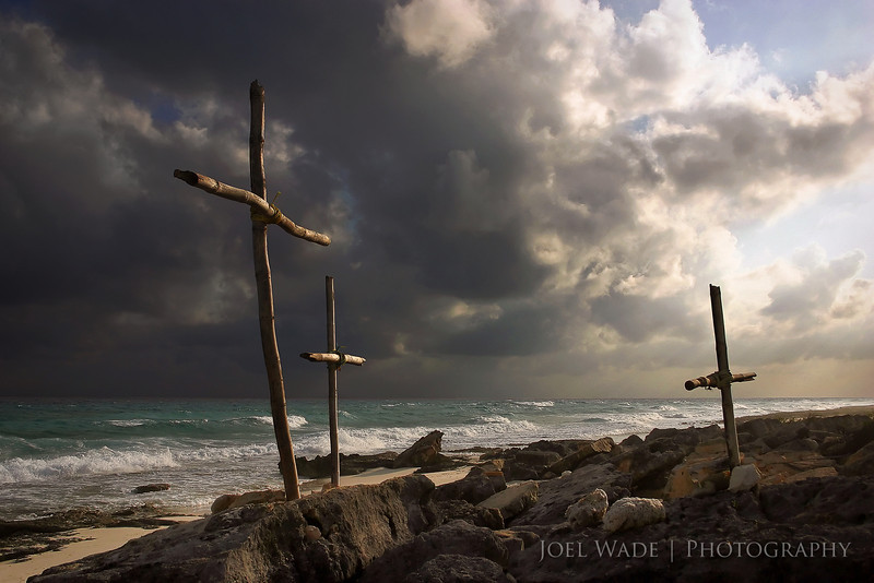 The Drowned<br /> <br /> This week I wanted to share a special shot from DEEP in the archives… one of my earliest shots that I still can look back on and be pleased with.  I spent Christmas of 2004 on the south-east coast of Mexico, and stumbled across these three make-shift crosses while taking a rented scooter around the island of Cozumel.  A restaurant around the corner explained that three locals had drowned there recently.  Frankly I lucked out here… the crosses are already emotionally powerful, but it happened to be late in the day close to golden hour, and a storm was blowing in from the Caribbean.    Hard to ask for more amazing skies to change the mood of the shot so dramatically versus puffy white clouds or boring overcast.<br /> <br /> Apologies for not posting in the last few weeks- turns out raising two children is even harder than raising one. Go figure.  I'll try to do better… Happy New Year to all!<br /> <br /> ISO 400, 24mm, f6.3, 1/4000s exposure.