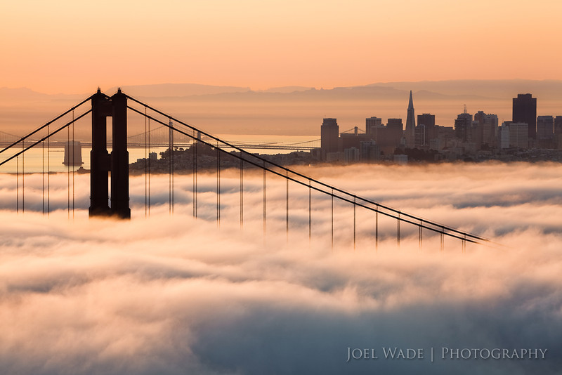 "Glorious Morning – Golden Gate Bridge, San Francisco<br />  <br /> I spent over four years chasing this shot.  It was so ridiculous it became known as my ""white whale"" to the friends who were kind enough to help ""fog spot"" for me.  I wanted a very specific look: the fog hanging low on the water so that the towers of the bridge protruded above it, the city visible, AND I wanted it to be during the ""golden hour""…  that first or last hour of sunlight when everything looks golden and warm.  San Francisco is well known for its thick fog- how hard could it be?  Fog it turns out is incredibly fickle.  Firstly, the fog rolls in all the time- especially in the evenings, but more often than not obscures the entire bridge.  Or it hangs just offshore.  Even when the conditions are perfect, it often only stays that way for less than an hour.  Many a time I'd spot the ""white whale"", quickly pack up my gear, make the drive over the bridge…. and it would be gone.  In desperation I ended up packing all my photo gear, a down jacket, warm hat, snacks, and even some reading material into a giant duffle bag- ready to go at a moment's notice.  I'd set my alarm for half an hour before dawn if the conditions looked promising, and race out to see if the fog was there.  After six failed pre-dawn attempts, I was finally lucky enough to get there in time for this beautiful scene just as the sun was rising.<br /> <br /> ISO 100, 200mm, f/14, 1/25s exposure.<br />  <br /> See more Golden Gate Bridge shots, including some from the same morning, and some foggy near-misses here:<br /> <br />  <a href=""http://joelwadephotography.com/Portfolio/Golden-Gate-Bridge/9764651_e3hdL#665695781_a4Hva"">http://joelwadephotography.com/Portfolio/Golden-Gate-Bridge/9764651_e3hdL#665695781_a4Hva</a>"