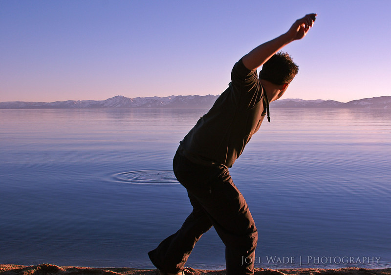 Skipping Stones – Lake Tahoe<br /> <br /> Shot this many years ago as a spontaneous candid of a friend after a long hard day of skiing in Lake Tahoe. Looking south from the north, the last rays of sun are illuminating just a smidge of the snowy peaks.  Wish I hadn't cropped off his feet, but I was at the widest FOV on the lens, and didn't have time to set back and recompose before the moment was gone.  Sometimes you get what you get, and it all works out anyway.<br /> <br />  ISO 400, 28mm, f/10, 1/250 second exposure.
