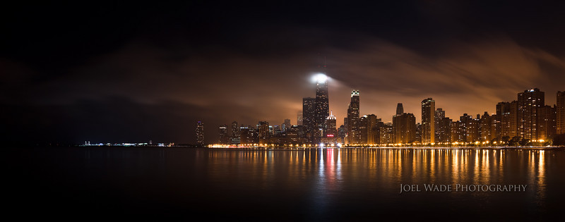 Chicago<br /> <br /> When you can put a world-class cityscape in front of a body of water, you can get some amazing reflections at night.  Throw in a little fast-moving fog and it gets even better.  The John Hancock building (the brightly lit tower near center) was popping in and out of visibility as the fog and clouds drifted past its massive 100-story edifice, so I needed to take a few tries to get a nice mix of visibility and brightly-illuminated fog.  So far this is my favorite image from my mini-vacation to both Chicago and NYC last week, but I still have some hunting to do…<br /> <br /> The image above was digitally stitched together from six separate vertical/portrait shots using a combination of both Lightroom and Photoshop.<br /> <br /> ISO 100, 17mm, f/13, 20s exposure