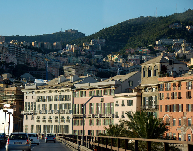 July 11 <br /> <br /> Driving through Genoa <br /> <br /> Most of the city of Genoa is built on the hills- with buildings of differing colours. This was taken from the highway connecting the center of the city to the suburbs - where we are located.